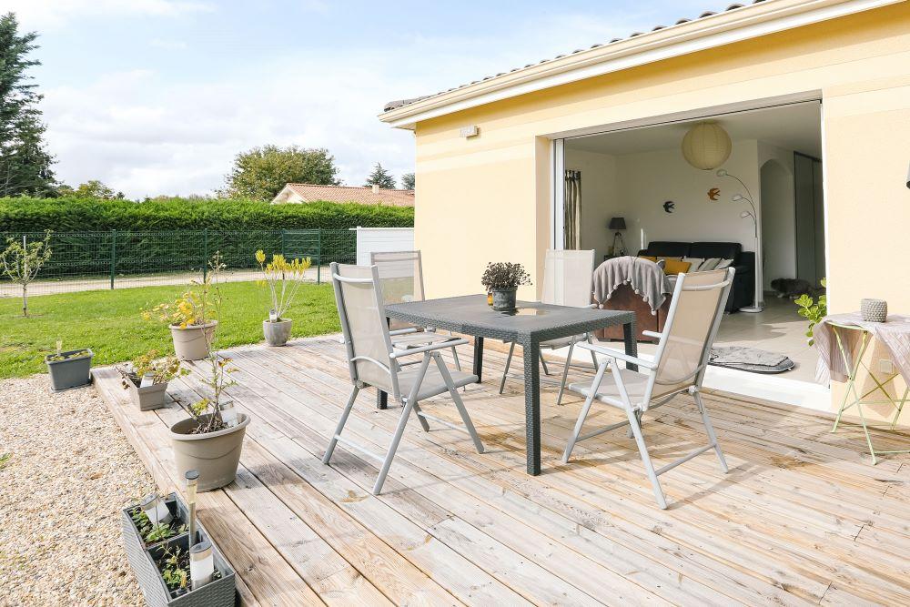 Terrasse en bois ouverte avec salon de jardin devant la grande baie-vitrée à galandage de la maison