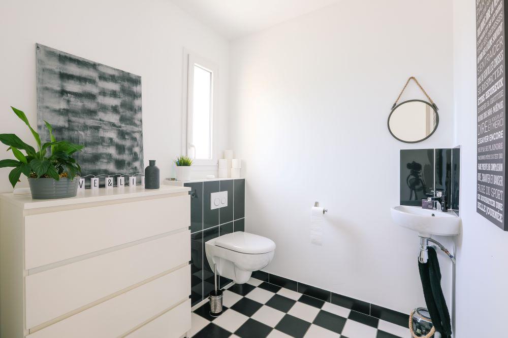 Grand toilette moderne avec WC suspendu et carrelage noir et blanc