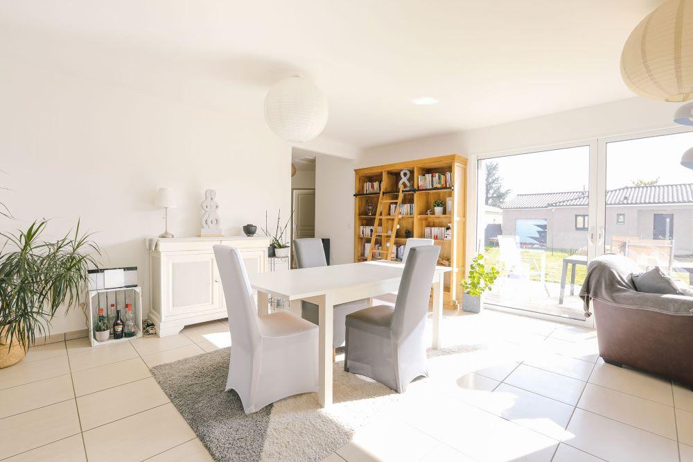 Espace salle à manger avec table et fauteuil contemporain devant une grande bibliothèque avec échelle