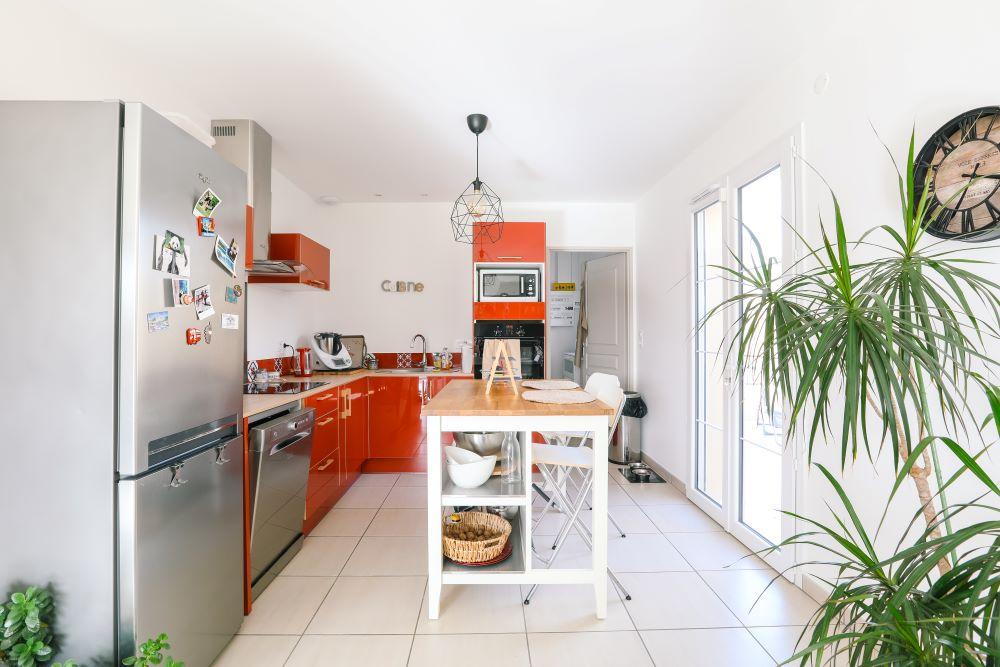 Cuisine équipée ouverte avec table pour manger et cellier attenant