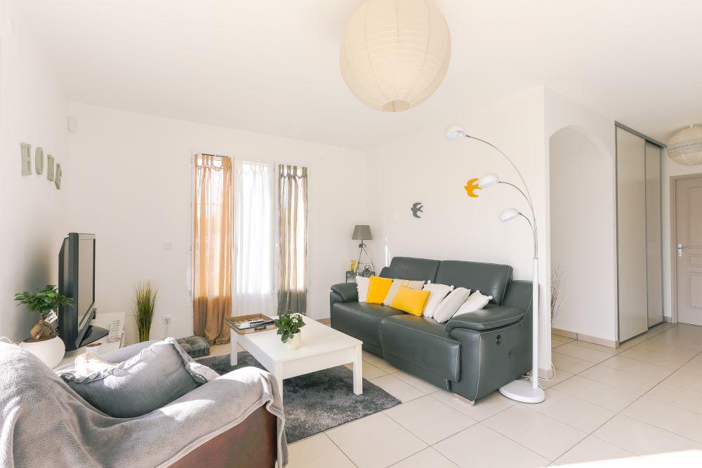 Salon lumineux avec un canapé, une télévision et un luminaire moderne