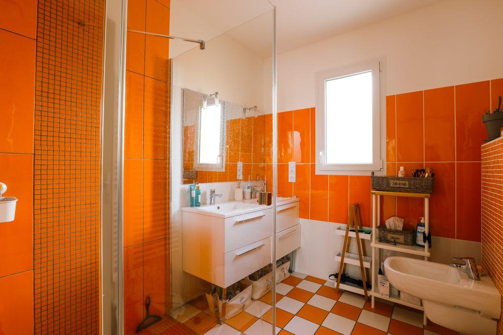 Salle de bains colorée avec meuble double vasque et douche à l'italienne