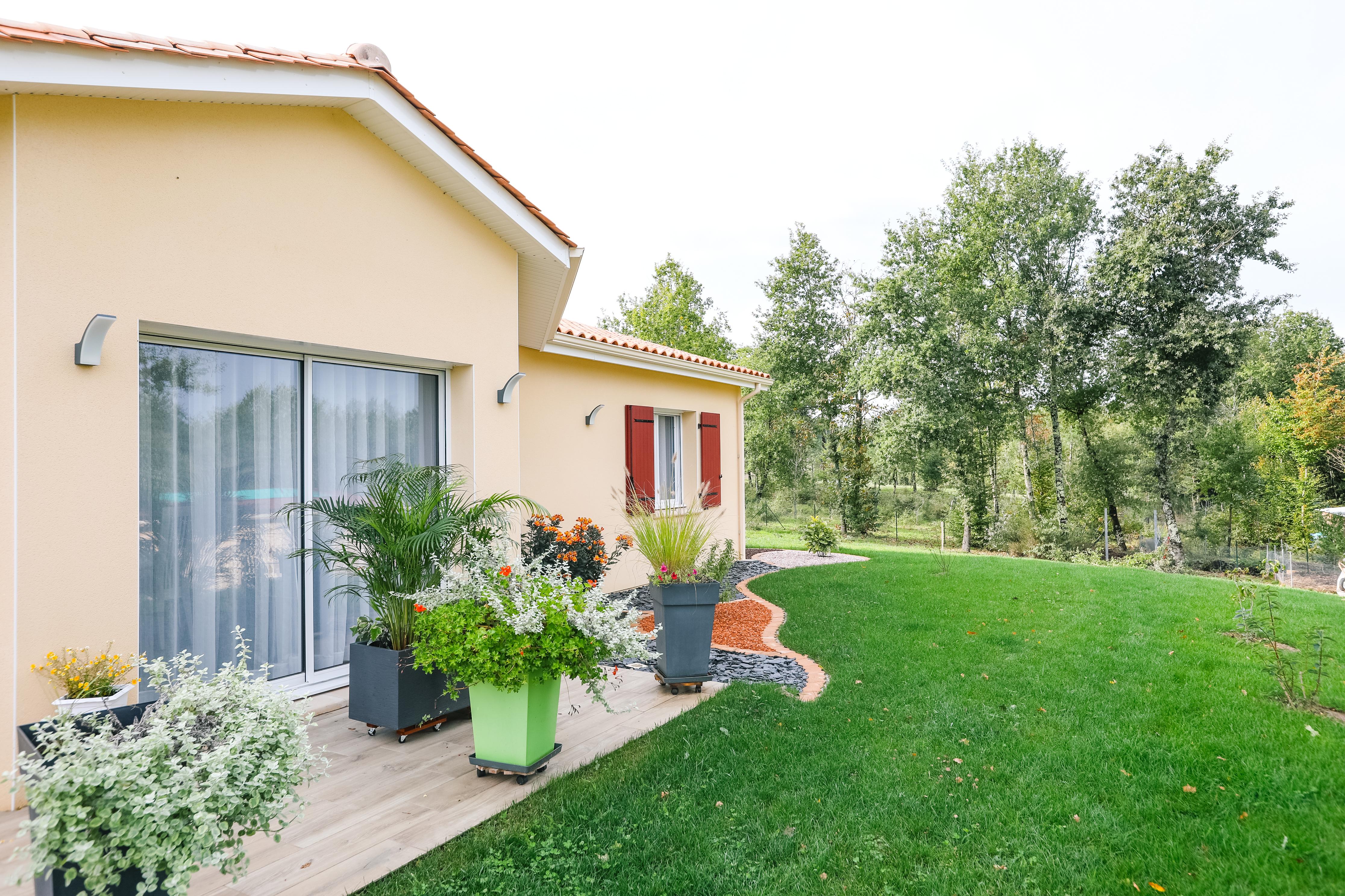 Vue de côté sur la terrasse fleurie avec vue sur le jardin