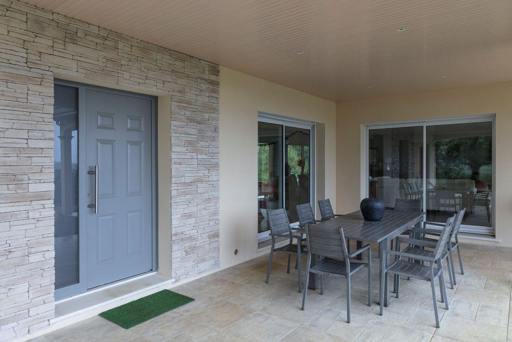 Entrée maison moderne avec porte tierce et pierres apparentes