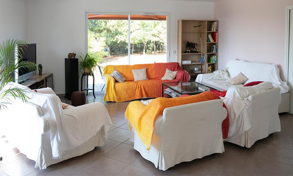 Baie vitrée avec canapés pour espace détente en Dordogne