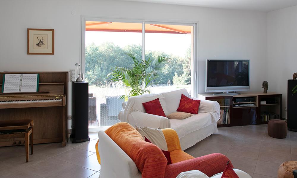 Grande baie vitrée avec piano et espace TV