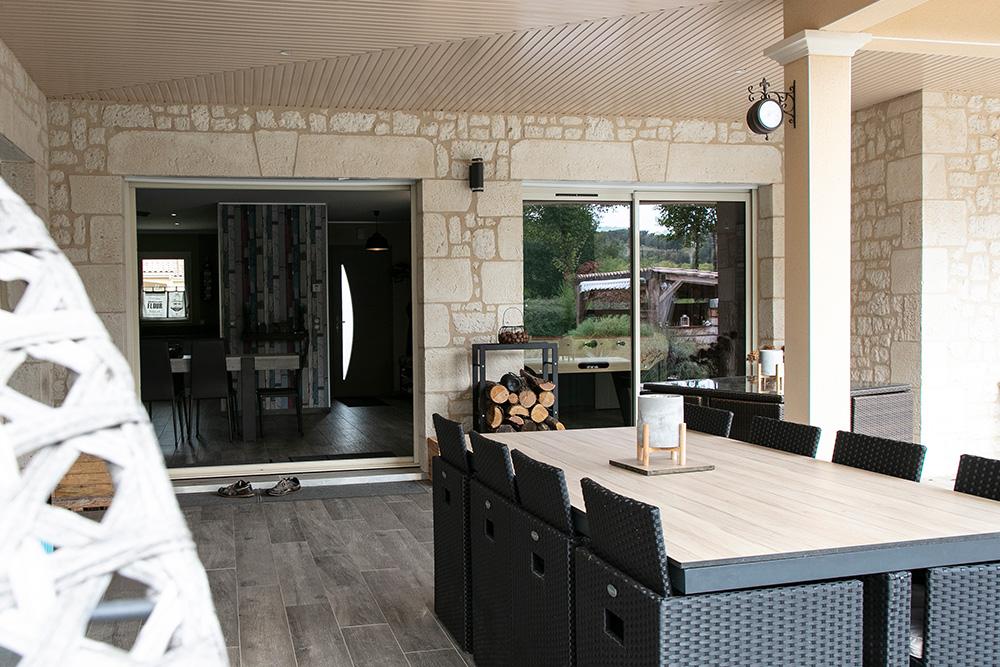 Terrasse couverte avec salon de jardin devant deux baies vitrées
