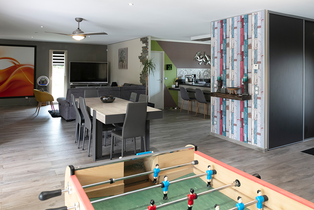 Salon et salle à manger avec table et baby-foot