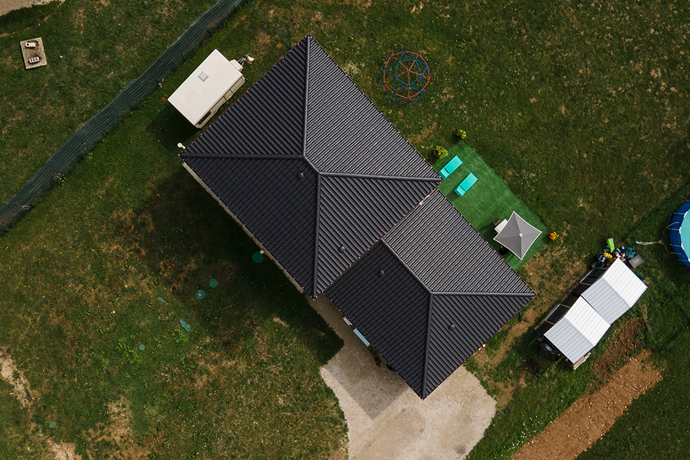 Maison moderne avec tuiles noires sur un grand terrain